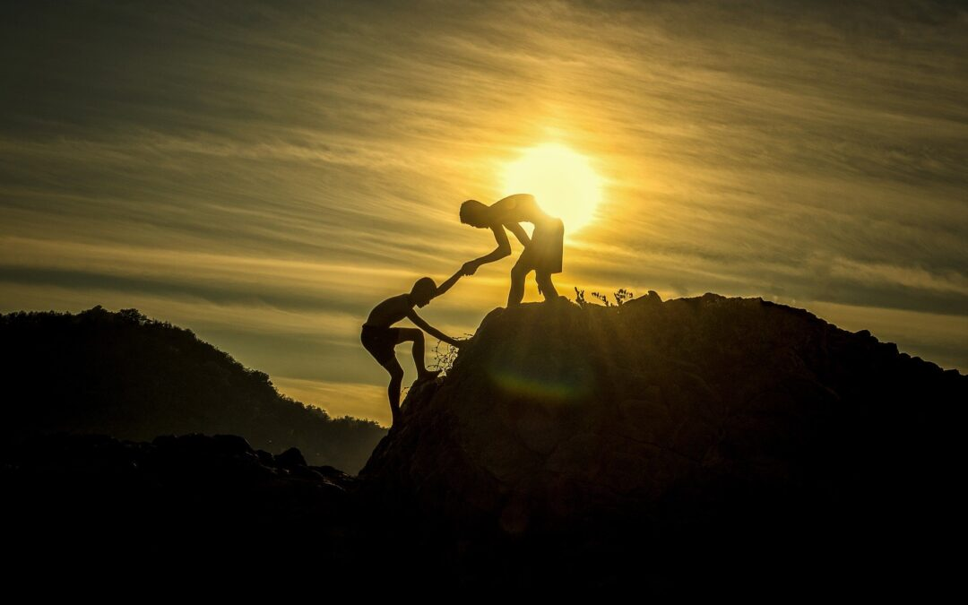 Two people helping each other climb a hill
