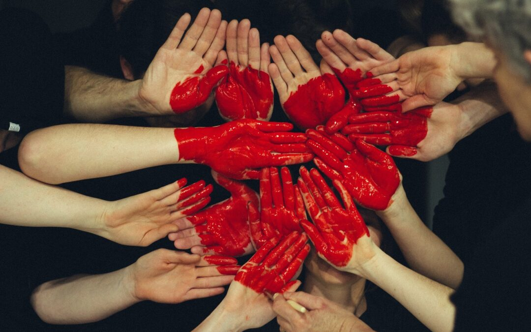 Using red paint a heart has been painted on top of numerous hands. Each hand representing a piece of the heart.
