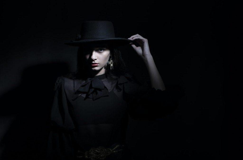 Woman wearing a black hat in a dark room.